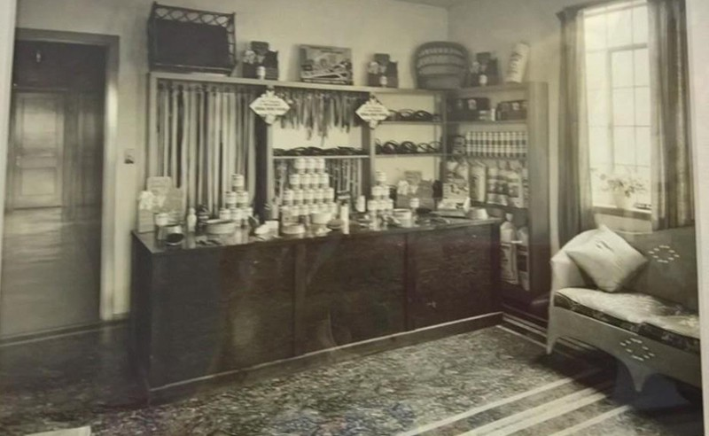 A black and white photo of the reception area and product display from the past
