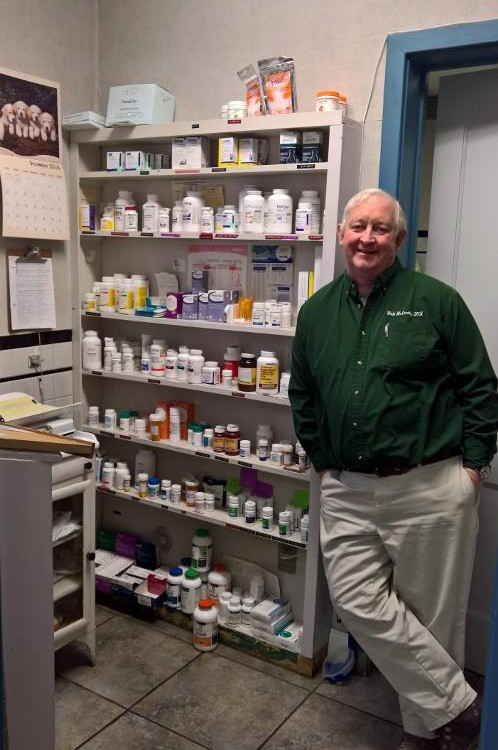 The veterinarian standing next to the office pharmacy